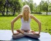 Blonde girl doing yoga in park — Stock Photo