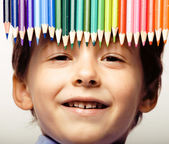 Little cute boy with color pencils close up smiling — Foto Stock