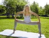 Blonde girl doing yoga in park — Foto de Stock