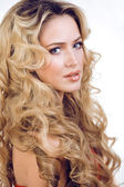 Beauty blond woman with long curly hair close up isolated — Foto de Stock