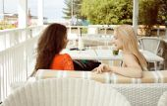 Portrait of two pretty friends in cafe drinking and talking — Foto de Stock