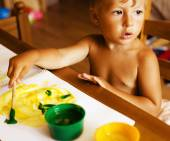 Portrait of little cute boy painting at home interior — Foto Stock