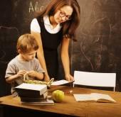 Little cute boy with teacher in classroom at blackboard — 图库照片