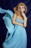 Young pretty blond woman in blue luxury dress — Stock Photo