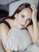 Pretty young brunette woman in bedroom interior — Stock Photo