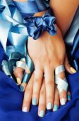 Blue manicure with ribbon close up as a gift — Stock Photo