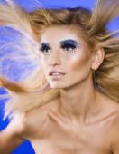Jonge vrouw van de schoonheid met creatieve make-up, haren vliegen — Stockfoto