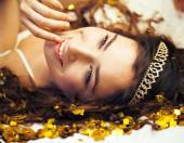 Beauty young girl in gold confetti and tiara, little princess celebration — Stock Photo