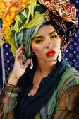 Beauty bright woman with creative make up, many shawls on head like cubian woman — Stock Photo