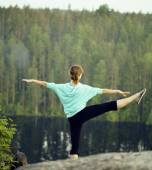 Cute girl making gymnastic on the top of mountain, lake down. — Stock Photo