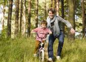 Father learning his son to ride on bicycle outside — Stock Photo