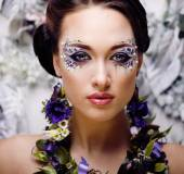 Floral face art with anemone in jewelry, sensual young brunette woman — Stock Photo