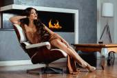 Beauty yong brunette woman sitting near fireplace at home — Stock Photo