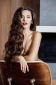 Beauty yong brunette woman sitting near fireplace at home — Stock Photo