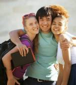 Cute group of teenages at the building of university with books huggings, back to school — Stock Photo