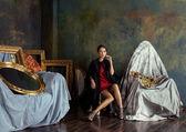 Beauty rich brunette woman in luxury interior near empty frames — Stock Photo