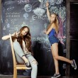 Back to school after summer vacations, two teen girls in classroom with blackboard painted — Stock Photo #57548717
