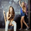 Back to school after summer vacations, two teen girls in classroom with blackboard painted — Stock Photo #57548739