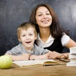 Little cute boy with teacher in classroom at desk — Stock Photo #57548757