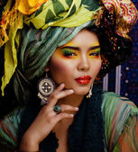 Beauty bright woman with creative make up, many shawls on head like cubian, ethno — Stock Photo