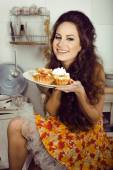 Crazy real housewife on kitchen smiling eating — Stock Photo