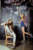 Powrót do szkoły po wakacyjnej, dwóch nastolatek w klasie z tablica malowane — Zdjęcie stockowe