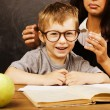 Little cute boy with teacher in classroom at blackboard — Stock Photo #58167463