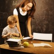 Little cute boy with teacher in classroom at blackboard — Stock Photo #58167469