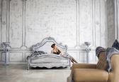 Pretty slim brunette woman resting in luxury room interior — Stock Photo