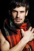 Portrait of handsome man warmed up in scarf christmas colored — Stock Photo