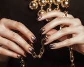 Close up photo hands with gold manicure holding chain — Photo
