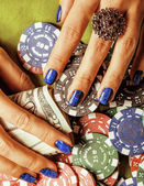 Hands of young caucasian woman with blue manicure at casino table close up, holding dollars — Stock Photo