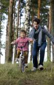 Father learning his son to ride on bicycle outside in park — Stock Photo