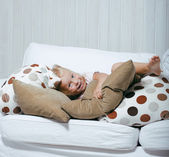 Little cute blonde girl playing at home with pillows — Stok fotoğraf