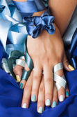 Manicure with ribbon close up as a gift, blue colored — Stock Photo