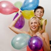Pretty family with color balloons on white background, blond wom — Stock Photo