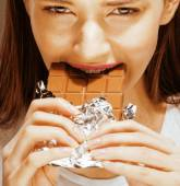 Cute young female with chocolate close up eating, — Stock Photo