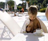 Little  cute boy at swimming pool warmed up with towel and hot t — Stock Photo