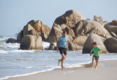 Happy family on beach playing, father with son walking sea coast — Stock Photo