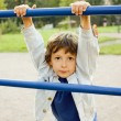 Little cute boy playing on playground, hanging on gymnastic ring — Stock Photo #64295353