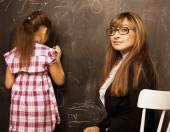 Teacher with pupil in classroom at blackboard writting — Stock Photo