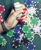 Hands of young caucasian woman with blue manicure at casino tabl — Stock Photo