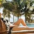 Young pretty woman at swimming pool relaxing in chair, fashion l — Stock Photo #70367399