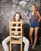 Back to school after summer vacations, two teen girls in classro — Stock Photo