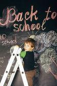 Little cute real boy at blackboard in classroom, back to school — Stock Photo