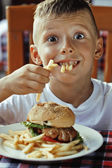 Little cute boy 6 years old with hamburger and french fries maki — Stock Photo