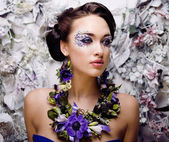 Floral face art with anemone in jewelry, sensual young brunette — Stock Photo