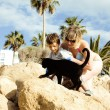Family playing with black cat in cyprus resort among palms — Stock Photo #76299245