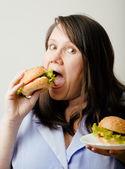 Fat white woman having choice between hamburger and salad — Stock Photo