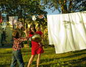 Happy family making laundry outside, children helping — Stock Photo